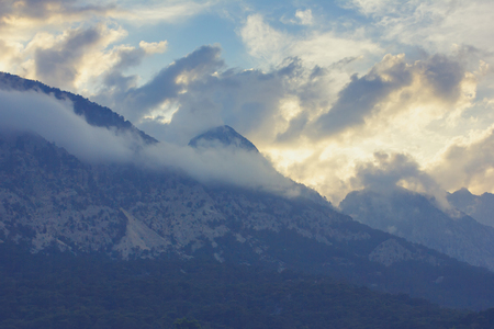 Breathtaking awesome mountain landscape with tops in clouds at sunset Lizenzfreie Bilder