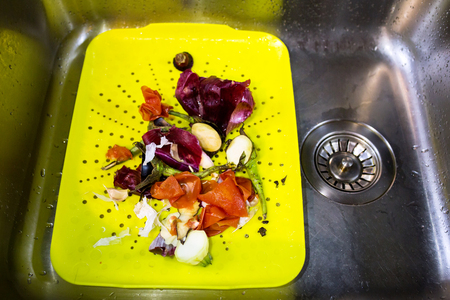 View of plastic dish in a sink full of domestic bio food waste, ready for composting, natural food recycling concept