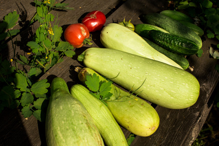Fresh summer vegetable crop on wooden background outdoors, top view, selective focus Stock Photo