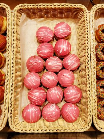 Sweet donuts with pink icing, pastries in basket in bakery shop, top view