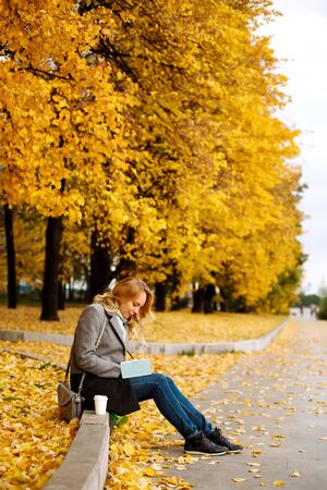 Woman sitting on a curb and writing something in her notebook in autumn park with golden trees Stock Photo