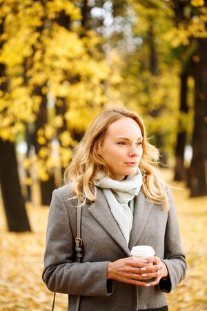Young confident woman with coffee outdoors in sunny autumn day, close-up portrait