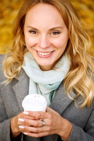Cheerful pretty woman holding paper cup of coffee in autumn park, looking at camera, close-up portrait