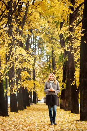 Blonde attractive woman walking at the nature in autumn time, good active day concept