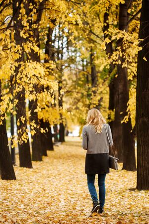 Woman walking away in autumn park with golden trees, full height