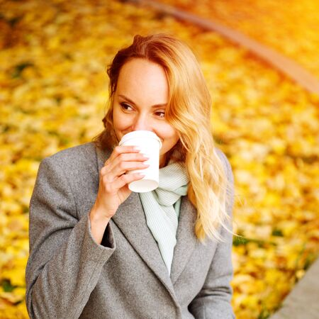 Cheerful pretty woman drinking coffee in autumn park, sunlight