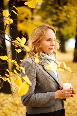Young smiling woman with coffee outdoors in sunny autumn day, close-up portrait Imagens
