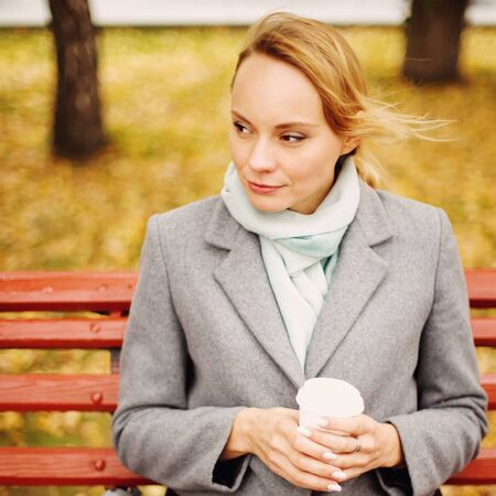 Pensive woman with coffee sitting on a bench in autumn sunny day, close-up Imagens