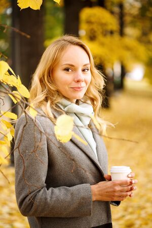 Young smiling woman with coffee outdoors in sunny autumn day, close-up portrait, looking at camera Imagens