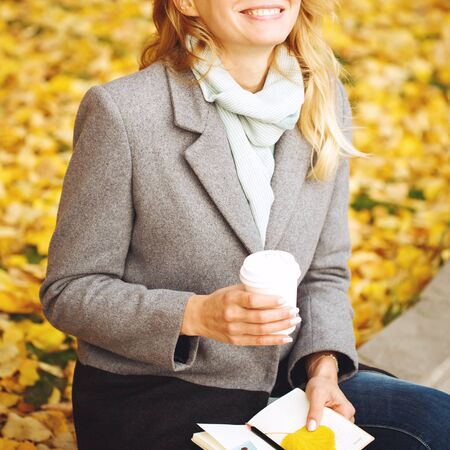 Happy creative woman with paper notebook and coffee drink outdoors in autumn sunny day Imagens