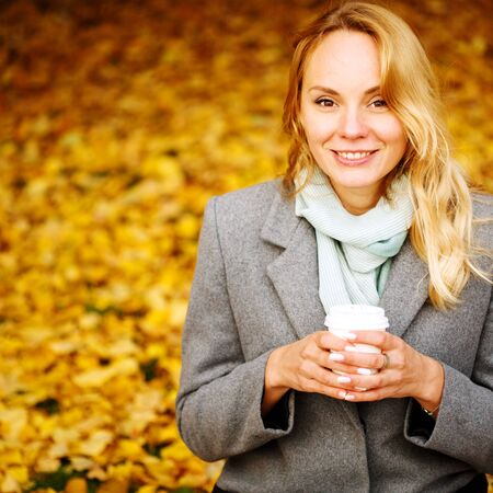 Cheerful pretty woman drinking coffee in autumn park in sunny day, looking at camera Imagens