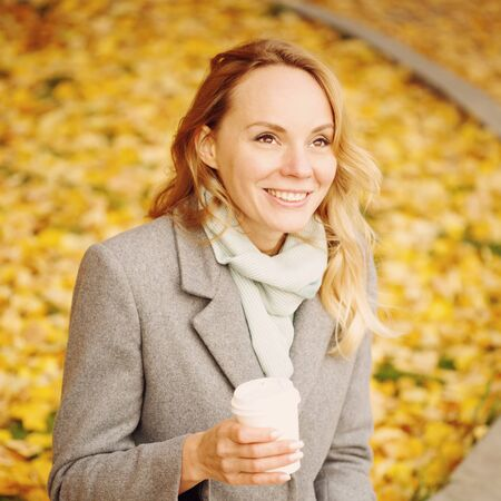 Happy creative woman drinking coffee outdoors in autumn park, sunny day Imagens
