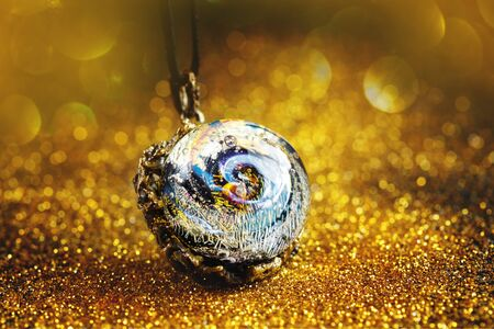 Creative jewelry made from glass with universe inside bead, on golden glitter, close-up view