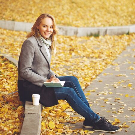 Woman sitting in autumn city park with golden trees around, looking at camera, image toned Imagens
