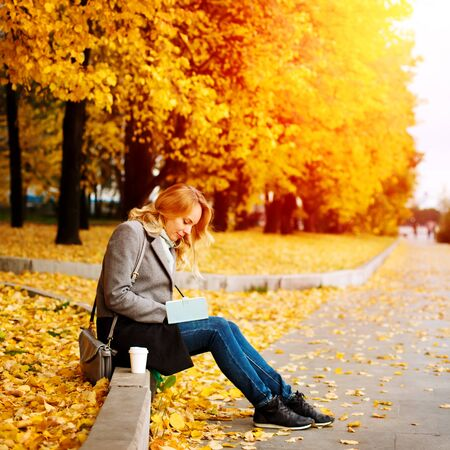 Woman sitting in autumn city park with golden trees around, writing something in her book Imagens