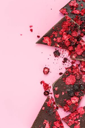 Broken dark chocolate bar pieces with dried red berries and crumbs on pink background