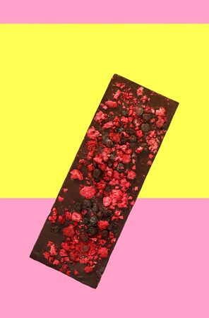 Chocolate with dried red berries on bright pink yellow background, top view 写真素材