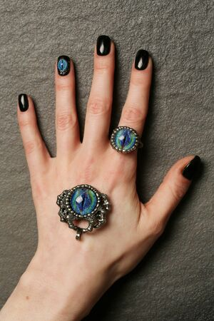 Unusual fantasy nail art and ring on manicured hands close-up, gothic style