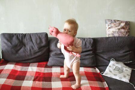 Dolce bambina in piedi sui suoi piccoli piedi su un divano a casa, giocando con il suo giocattolo morbido drago, guardando la telecamera, a tutta altezza