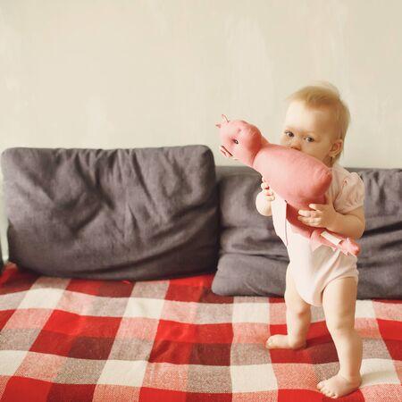 Sweet baby girl standing on her little feet on a couch at home, playing with her soft dragon toy, looking at camera, full height