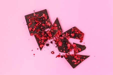 Broken black chocolate bar pieces with scattered dried red berries on pink background, flat lay Stok Fotoğraf