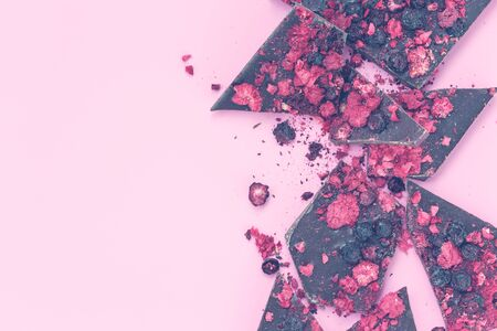 Broken black chocolate bar pieces with scattered dried red berries on pink background, flat lay withj space, valentine`s card concept, vintage colors