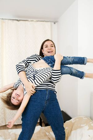 Young woman having fun with her cute little baby holding her upside down and playing like on a guitar, funny games