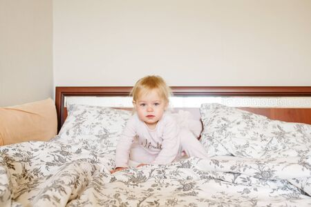 Cute little blonde infant girl just woke up in the morning sitting in parent s bed alone, full body looking at camera
