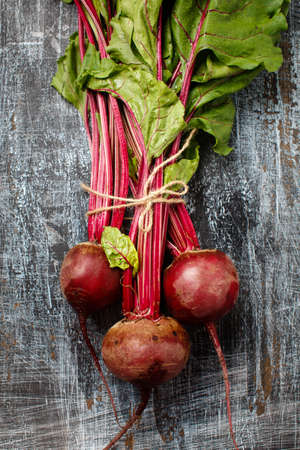 Bundle of fresh organic farmer young beetroots on dark scratched background, close-up, top view. Natural organic vegetables.