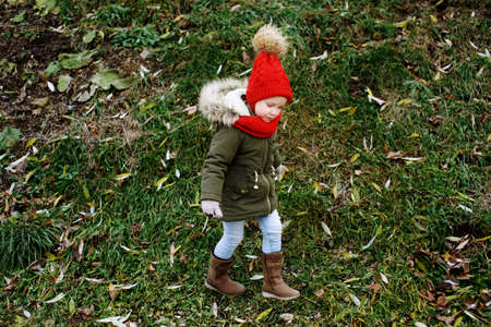 Cute little funny girl in trendy outfit walking outdoors in fall park, children fashion, full body portrait