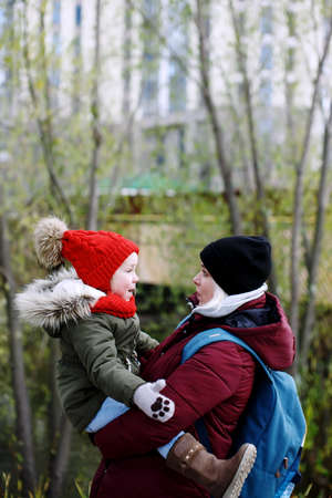 Young mother holding her daughter on hands, walking outdoors looking at each other