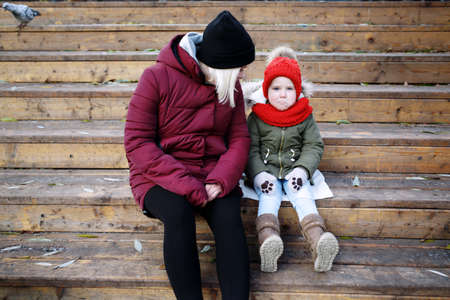 Young mother talking to her cute little daughter outdoors sitting together in warm clothes on wooden stairs Standard-Bild