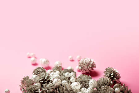 Christmas festive composition with silver pine cones and small glitzy balls on bright pink background, copy space
