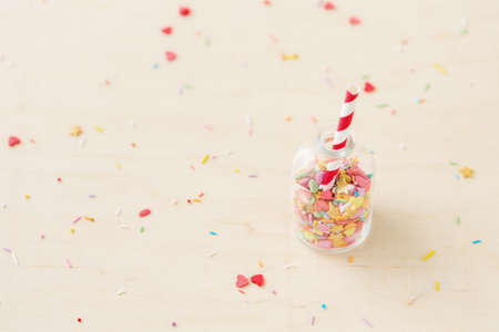 Colorful heart and star sprinkling in a little bottle with striped red and white straw, selective focus