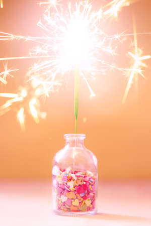Burning sparkler in a bottle with colorful sprinkling, festive celebration party concept, selective focus Stock Photo