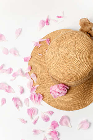 Summer, spring concept, straw braided hat, pink peony flowers and petals on white background, top view