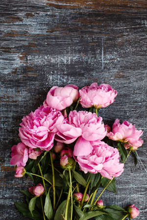 Fluffy bouquet of pink fresh peony flowers on scratched shabby dark wood, flat lay Stock Photo