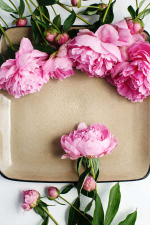 Simple flat lay flower frame of pink peonies, spring and summer season concept