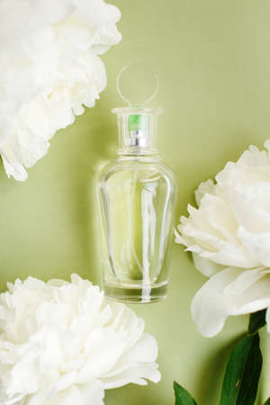 Transparent mockup glass bottle with perfume among fresh white peony flowers on olive green pastel color, top view