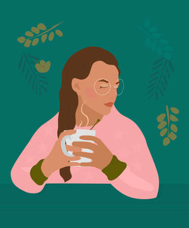Сute girl with braid holds cup with a hot drink in her hands.There is steam from a mug with tea, cacao or coffee.Cozy autumn mood.Young woman portrait with glasses and freckles. Pink casual sweatshirt