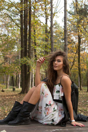 stilish: Young woman, girl, sitting in white floral dress, on the bench in the autumnal forest Stock Photo