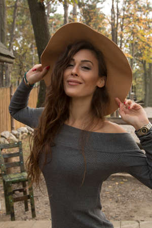 stilish: Beutiful girl in the forest with autumn fashion style with brown hat