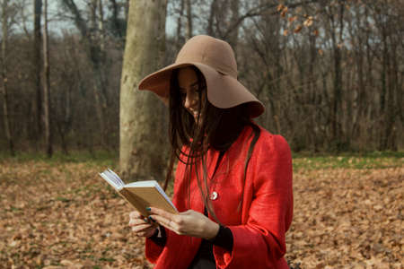 Girl with hat reading book in forest