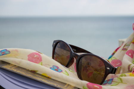 scarf beach: Sunglasses, book and scarf in the beach Stock Photo