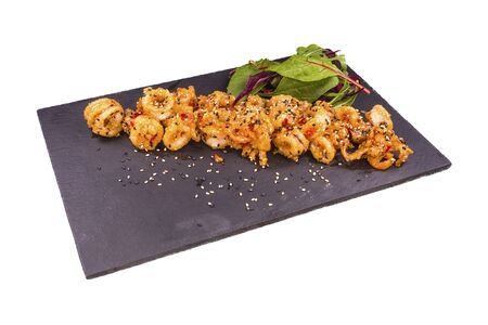 Gourmet fried squid Yakuza and sesame on a black stone plate, isolated on white background