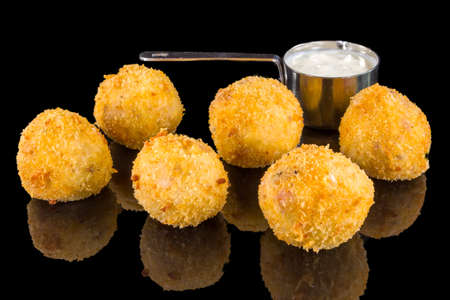 Tasty balls from rice and cheese with reflection, isolated on black background