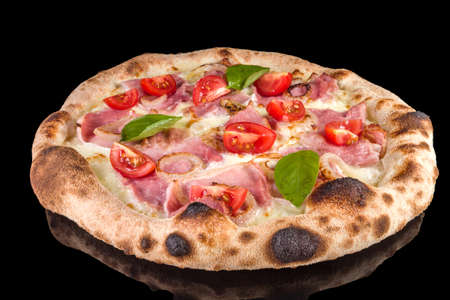 Delicious pizza with speck Cotto, mozzarella, sour cream, onion, tomatoes,  with reflection, isolated on black background