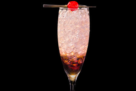 Colorful Kir Royale cocktail, with ice cubes in a glass, isolated on black background Stock fotó