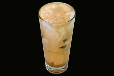 Delicious freddo Cappuccino with ice cubes in a glass, isolated on black background