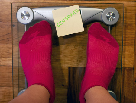 Digital weight scale with note covering screen Stock Photo